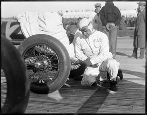 Famous auto racer R. De Palma pins his baby's shoe on his auto for luck before race in Rockingham, N.H.