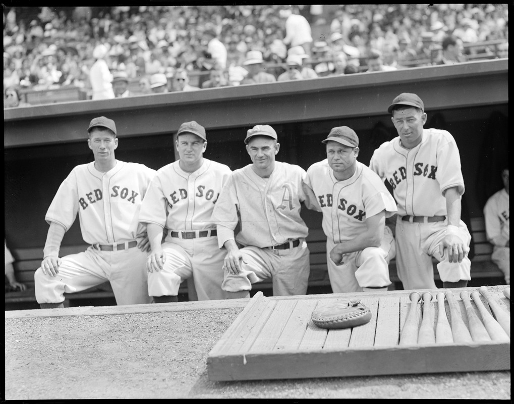 Athletics player poses in dugout with Red Sox players. (Far left Lefty Grove, Jimmie Foxx 2nd from right)