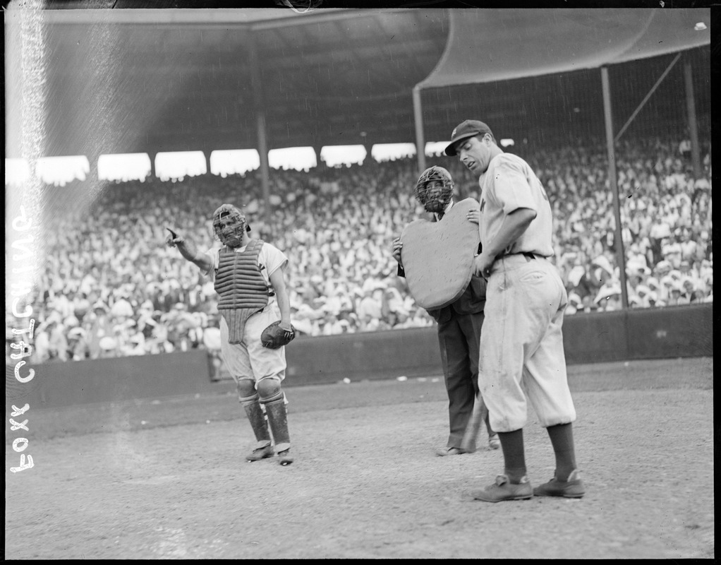 Catcher Jimmy Foxx of the Red Sox points to the outfield as DiMaggio of the Yankees and the umpire looks on