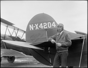 Wilmer Stultz standing side of tail of Byrd's 3-motor fokker that flies to the South Pole. Plane Friendship