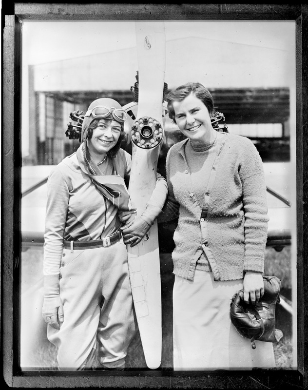 17-year-old aviator Elinor Smith posing next to propeller with 18-year-old golf star, Helen Hicks. Fairchild Field, Farmingdale, N.Y.