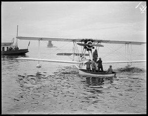 Seaplane from SS Ile de France lands mail in Boston Harbor after leaving the liner 300 miles off Nova Scotia and landing 10 hours later, saving 30 hours. Deer Island light in background.