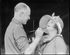 """One of the """"Around the World"""" aviators paints a woman at East Boston Airport"""
