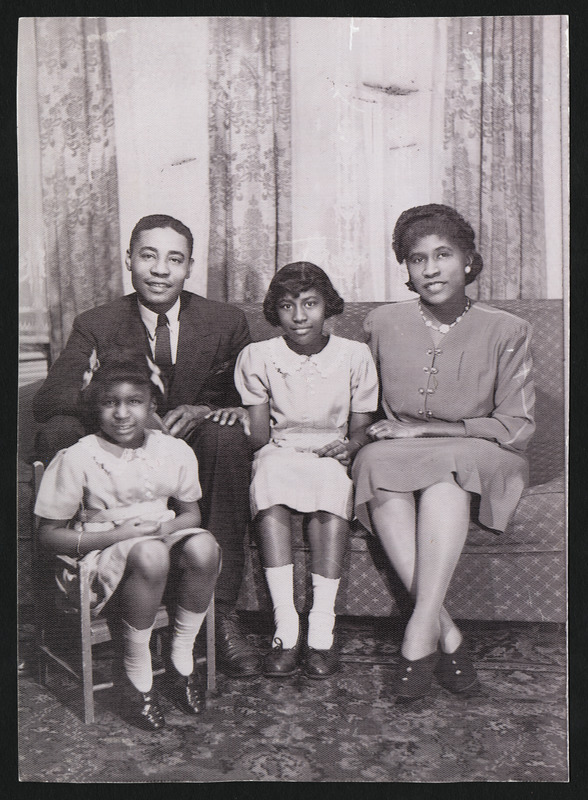 """Brandford Burke, Keitha's father, Henrietta """"Yetta"""" Burke (nee Brown), Keitha's mother, and Keitha Burke Hassell. Beverley Burke (Keitha's sister) on chair"""
