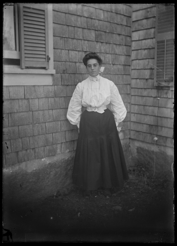 Woman at angle of house outdoors