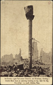 An electric light post corner Third St. and Broadway, showing a granite block from an adjoining building on top. After the big fire of Apr. 12, 1908. Chelsea, Mass.