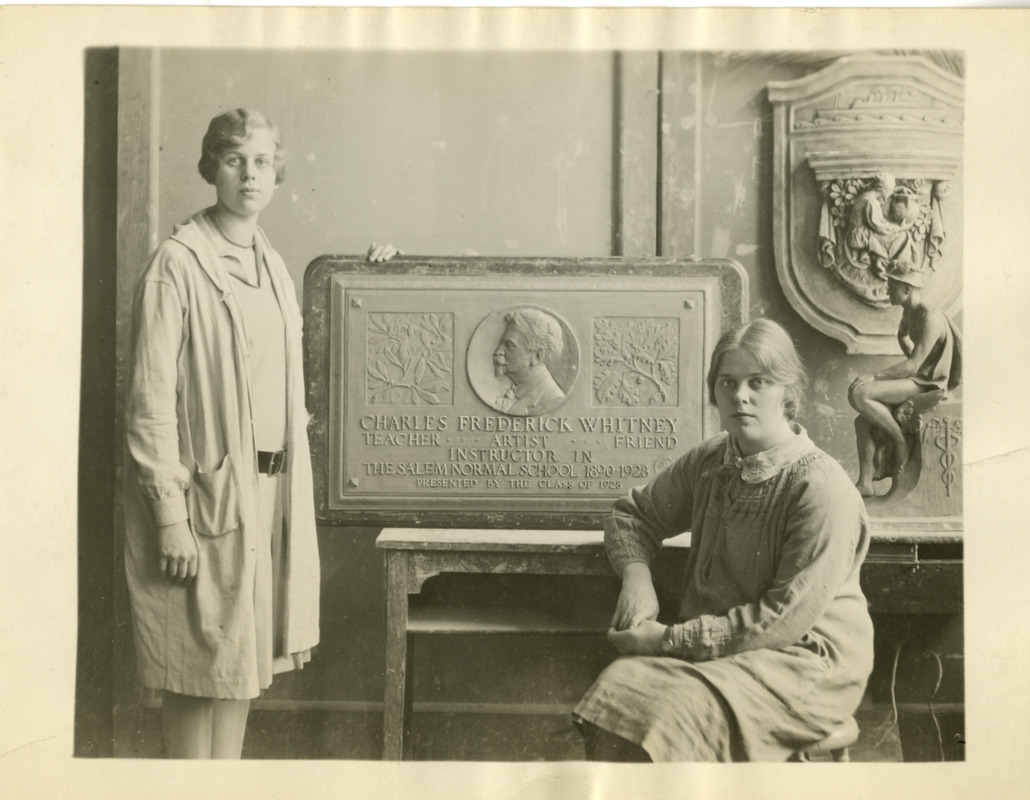 Two students with plaque memoralizing Charles Frederick Whitney