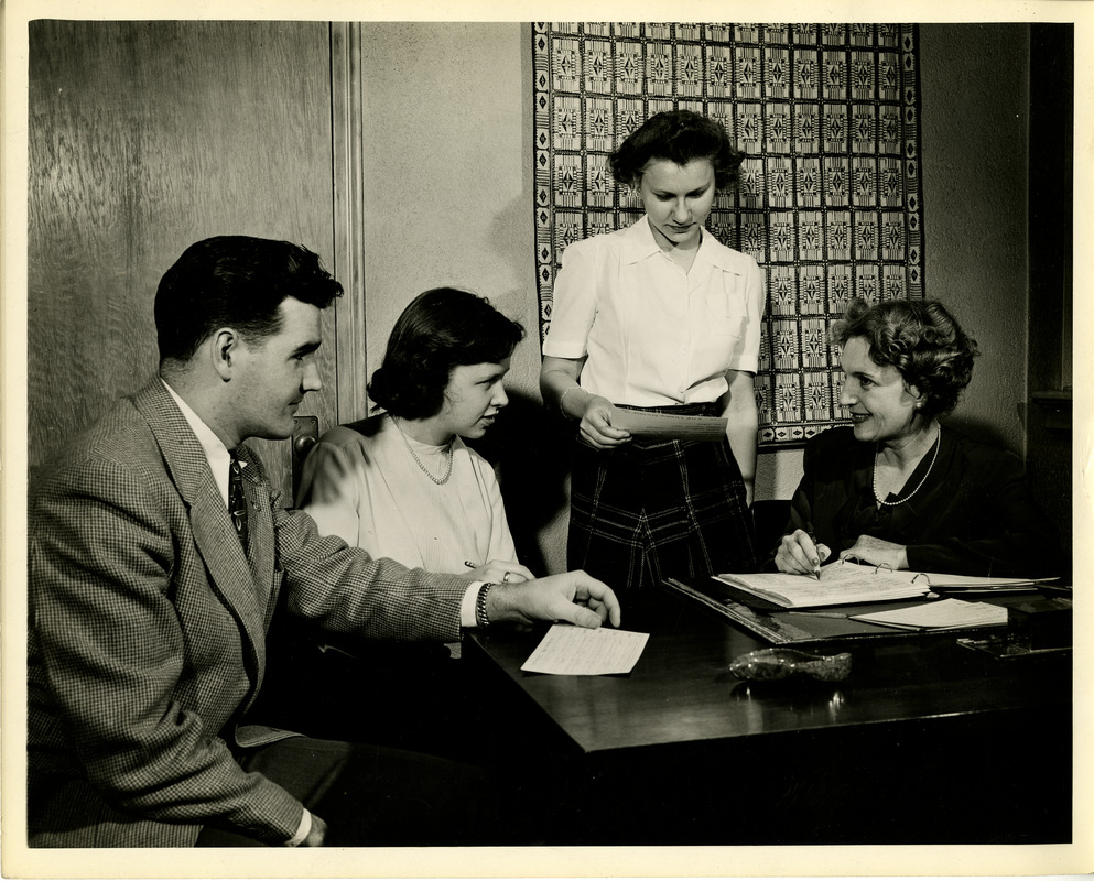 People in conversation at desk