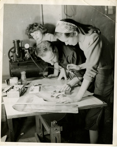 Woman using an airbrush while two people watch