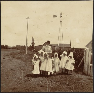 Woman with several young girls in white frocks standing in street near windmill