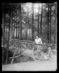 Woman with bicycle in woodlands