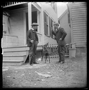 2 men and dog in front of house