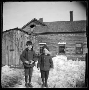 2 children outside of house in winter