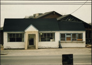 Wooden building with two windows boarded-up