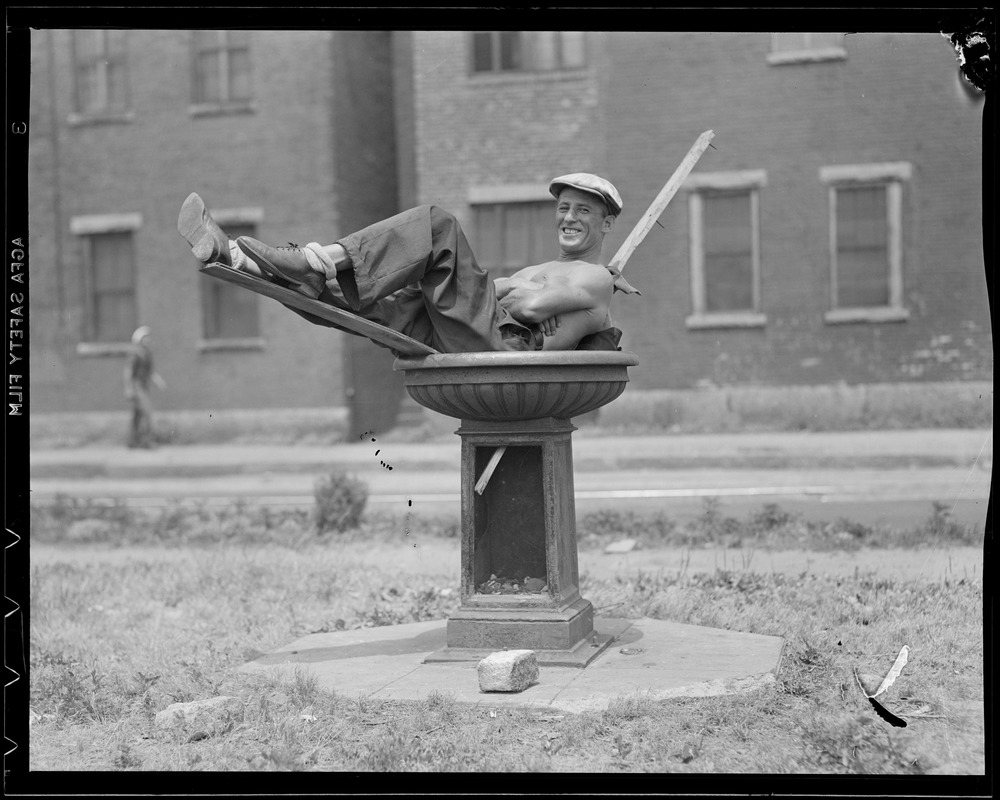 Man cooling off in bird bath on hot day