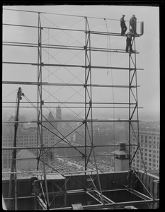 Workers building sign on roof of building near Park Square