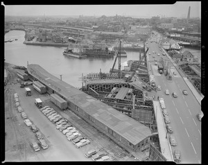 "Aerial views, overpass harbor, old ""Charlestown"" bridge. (Shows Warren Avenue Bridge and Yard 12, behind North Station. View: northwest, lighter at work in Charles River building pier support for North East Express Way. Millers River, left; Bunker Hill Monument, right.)"