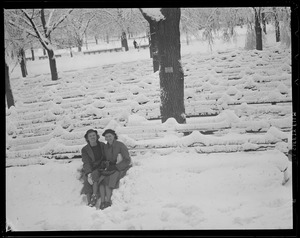 Women clear seat on benches on Boston Common on snowy day