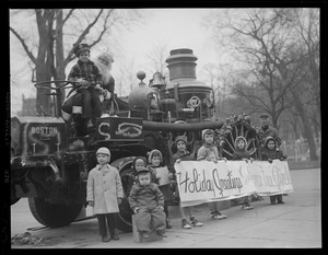Children pose with steam fire engine decorated for Christmas, on Common