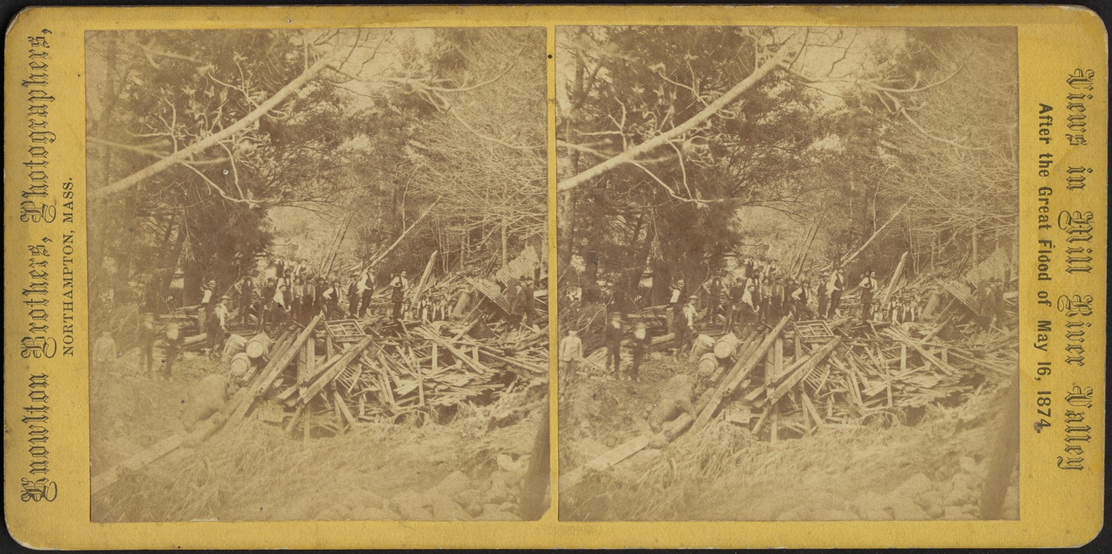 Group of men standing by a pile of timber and debris left by the Mill River Valley flood