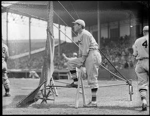 Baseball player Dizzy Dean, Boston, leaning on bats.