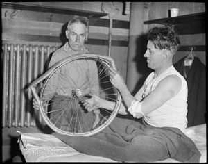 Reggie McNamara examines damaged wheel after being thrown at Boston garden