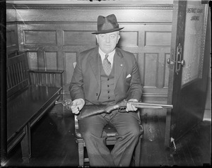 Chief John Cahill of Dedham holding shotgun and revolver used in attempt by Edward Frye to free Millens.