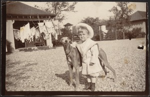 Small boy with greyhound; house with laundry hanging in background