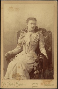 Young woman in light dress with white ruffle collar; seated in ornately carved wooden chair