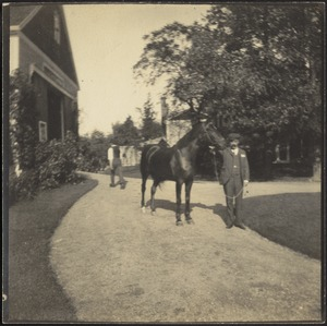Man with horse in front of barn