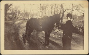 Ashdale Farm. Saddled horse on dirt road; woman, possibly Gertrude S. Kunhardt, in riding clothes