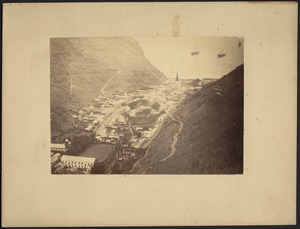 Birds-eye view of village and harbor in mountain valley; three-masted ships in distance
