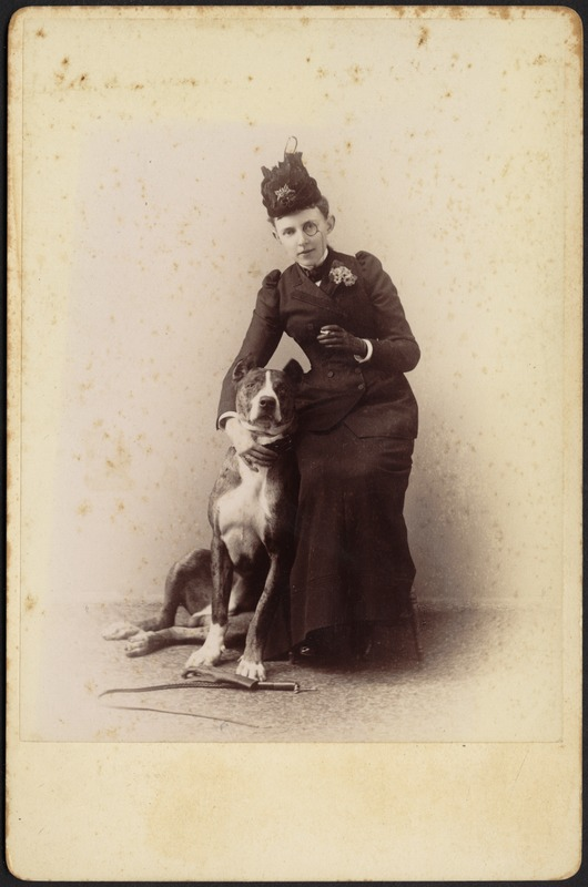 Studio portrait of unidentified woman in black dress and monocle with cigarette posing with Great Dane; whip and glove on floor