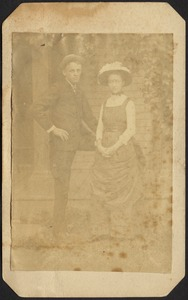 Young man and woman standing in front of house