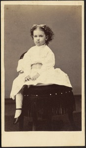 Young girl in white frock seated on dark chair with fringe