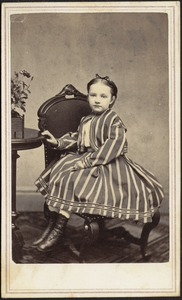 Young girl in striped dress seated in chair, hand on table