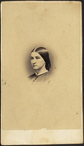 Young woman with dark hair pulled back into netted bun (head and shoulders)