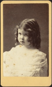 Young girl with dark hair, shoulder-length ringlets, white frock