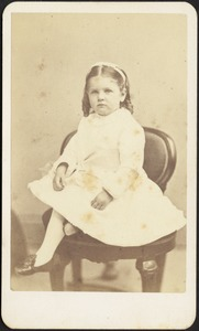 Young girl in white dress and bow seated on chair
