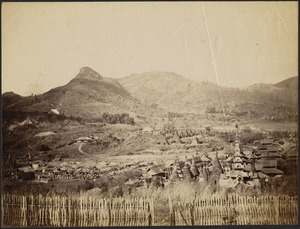 View from wattle fence of rural Burmese village, featuring ancient stone temples with conical spires and a wooden pagoda structure; people and livestock gathered near straw huts on left; mountains in distance