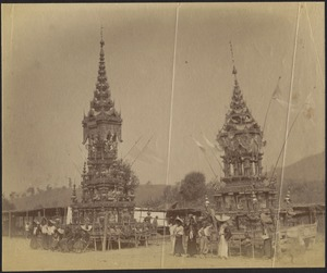 View of rural village; men and women gathered in front of two ornately painted wooden pagoda temples