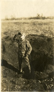 Soldier standing in blast crater, ca. 1918