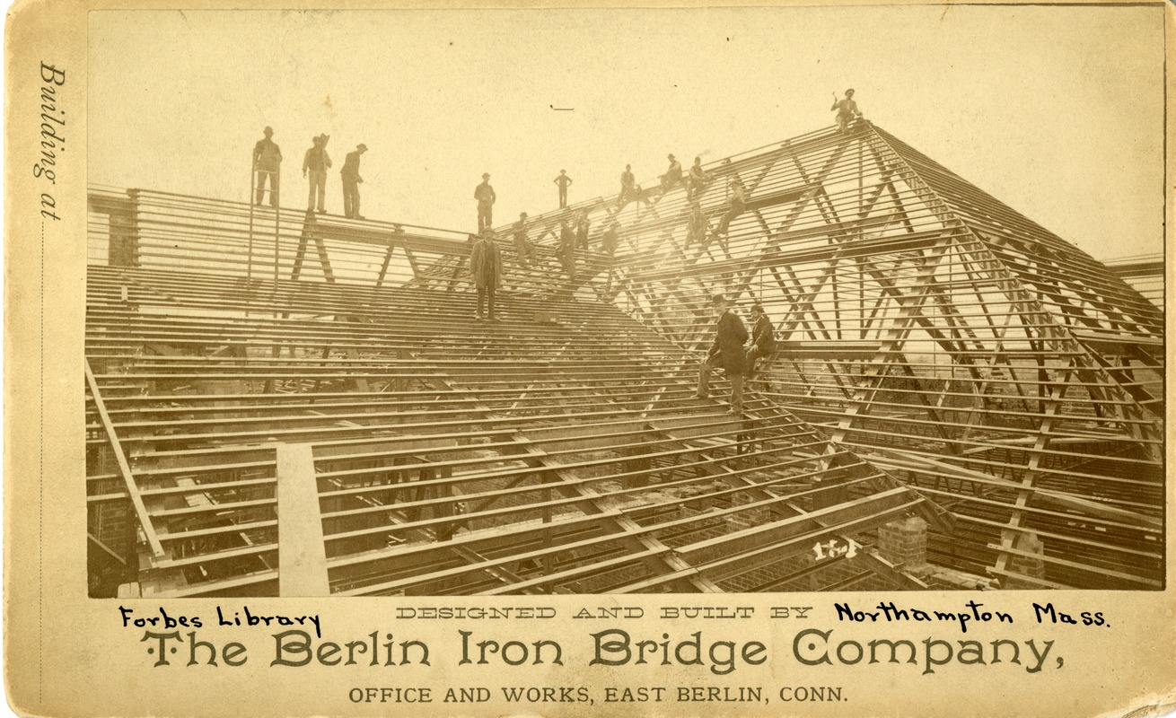 Laborers from the Berlin Iron Bridge Company at work on building the roof of the Forbes Library