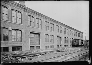 Two story warehouse along railroad spur, showing railroad car 1900-1907