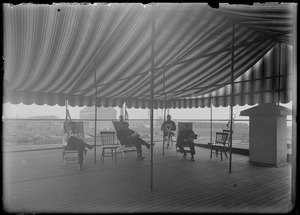 Group of men sitting under roof-top pavilion, wharves in background - grain elevator, ship, freight cars, (B.W.C. employees?)
