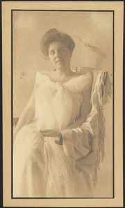 Isabel in loose white dress, seated