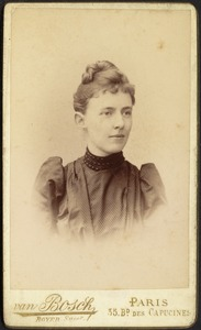 Young woman in dark dress with strips; hair in top knot