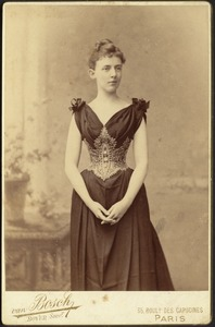 Young woman in dark dress with elaborate corselette