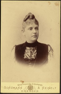 Young woman in high collar dress with black velvet vest