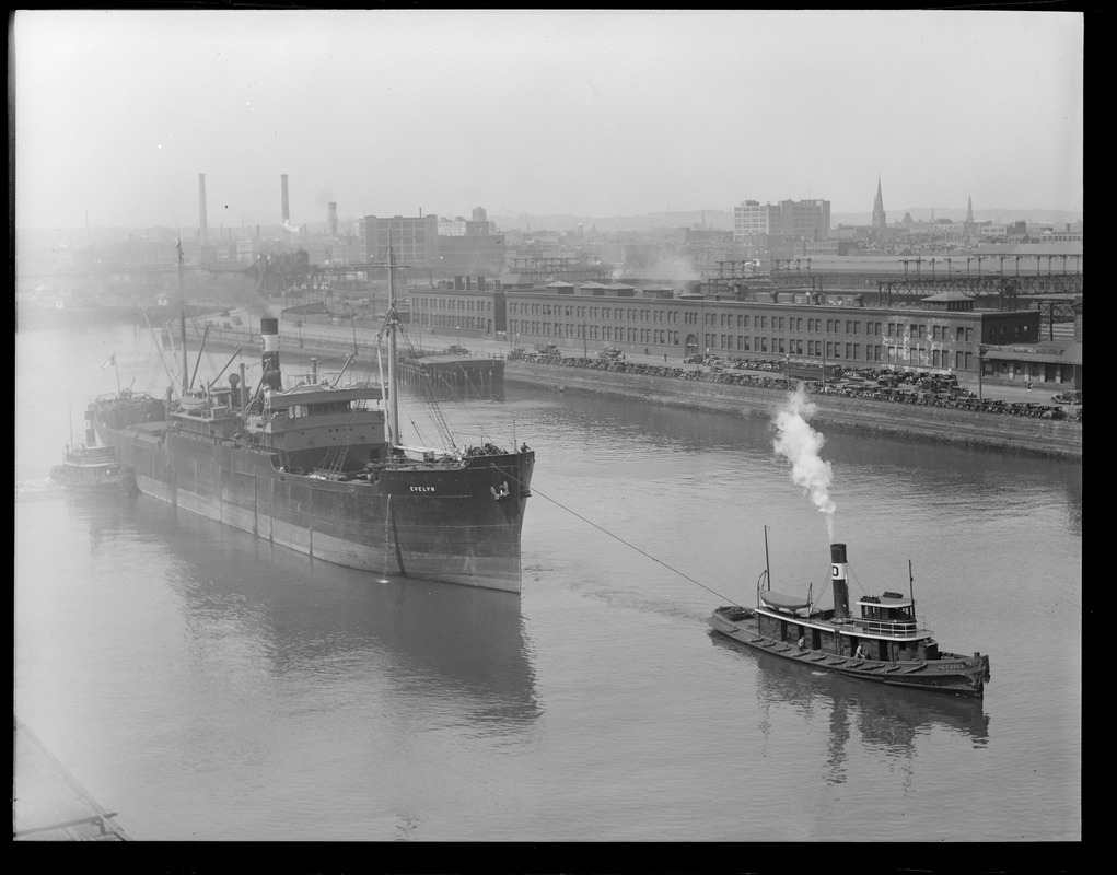 Bull line sugar boat SS Evelyn towed up Fort Point Channel by the tug Leader, alongside the South Station power house